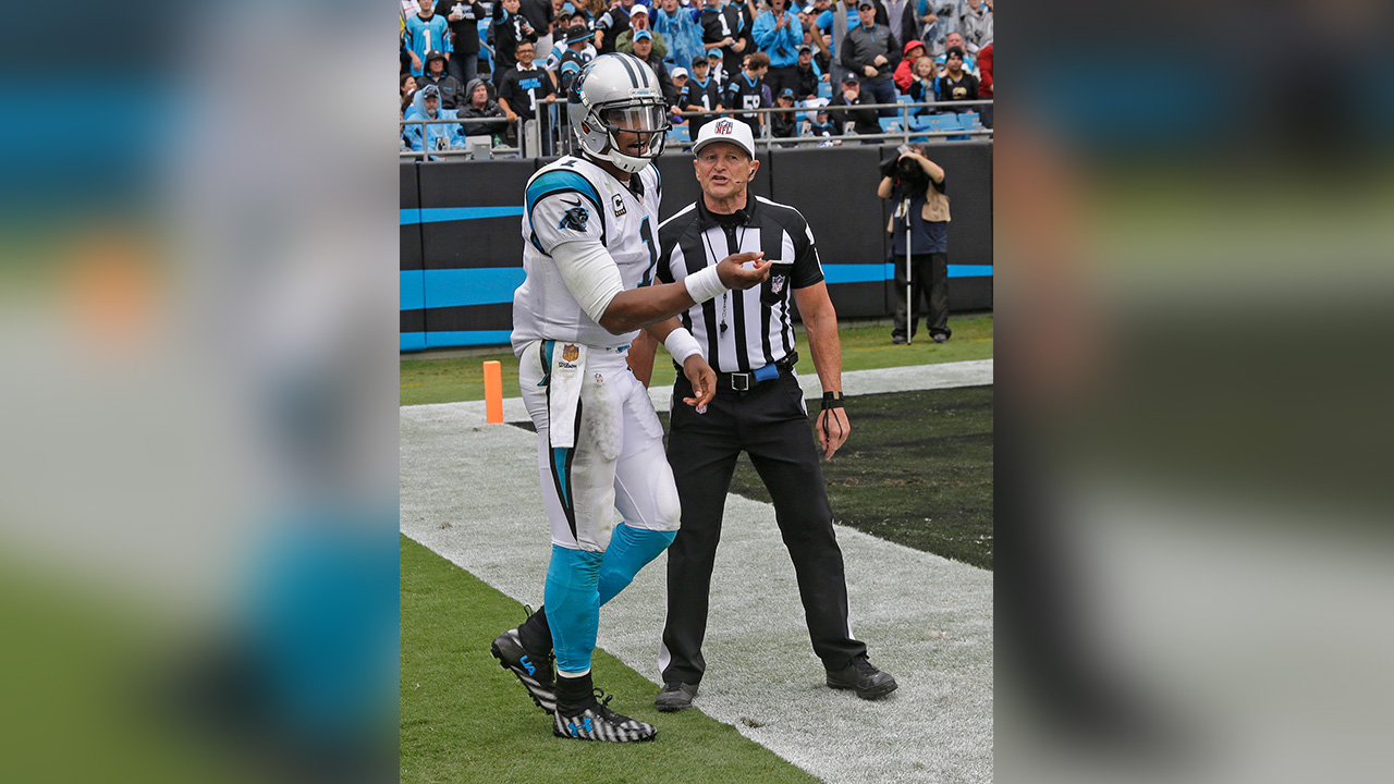 Sept. 27, 2015 photo of Carolina Panthers' Cam Newton, left, talks with referee Ed Hochuli, right, after being hit on the sidelines in the second half