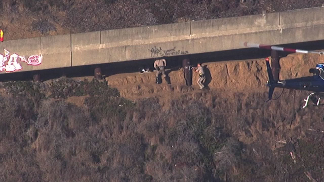 California Highway Patrol officers detain a man hiding underneath the roadway on Treasure Island, Sept. 28, 2015.
