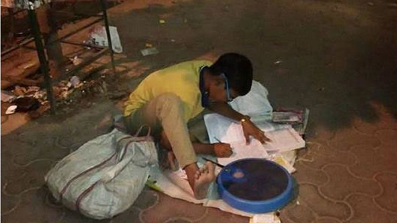 Indian boy studying on street