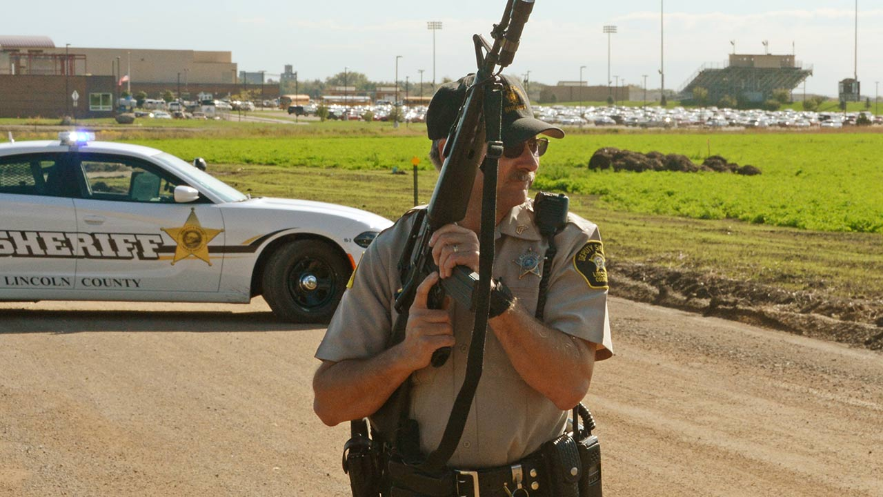 An armed Lincoln County deputy sheriff blocks the entrance to Harrisburg high school following a shooting at the school Wednesday, Sept. 30, 2015 in Harrisburg, S.D.
