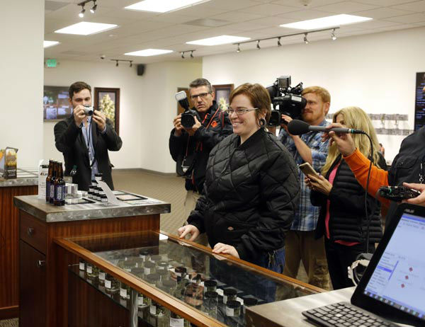 """<div class=""""meta image-caption""""><div class=""""origin-logo origin-image none""""><span>none</span></div><span class=""""caption-text"""">Davia Fleming, 29, center, is surrounded by media members as she becomes the first shopper at Shango Premium Cannabis, in Portland, Ore., Thursday, Oct. 1, 2015. (AP Photo/ Timothy J. Gonzalez)</span></div>"""