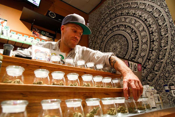 "<div class=""meta image-caption""><div class=""origin-logo origin-image none""><span>none</span></div><span class=""caption-text"">Shane Cavanaugh, owner of Amazon Organics, a pot dispensary in Eugene, Ore., arranges the cannabis display in his store. (AP Photo/ Ryan Kang)</span></div>"