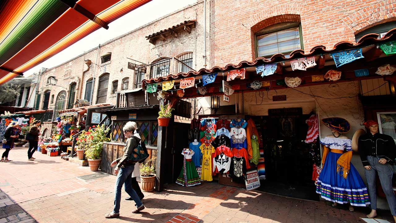 In this file photo, tourists shop at Olvera Street stores at El Pueblo de Los Angeles Historic District in Los Angeles.