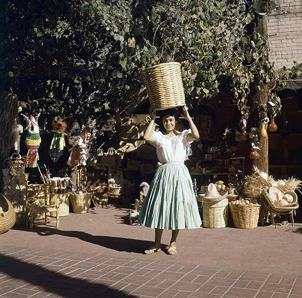 Olvera Street market set up along street. Salesgirls pose with products in Los Angeles in December 1962.