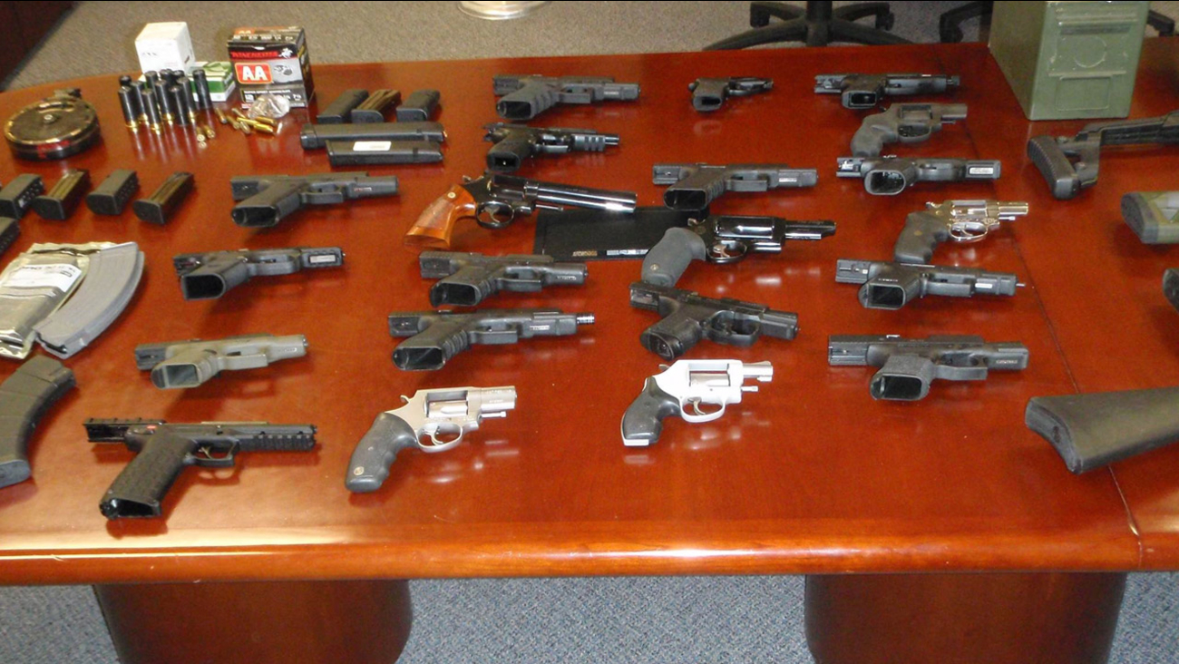 Guns, including assault weapons with high-capacity magazines and shot guns, are shown along with ammunition from the raid at the Victorville home on Wednesday, Sept. 30, 2015.