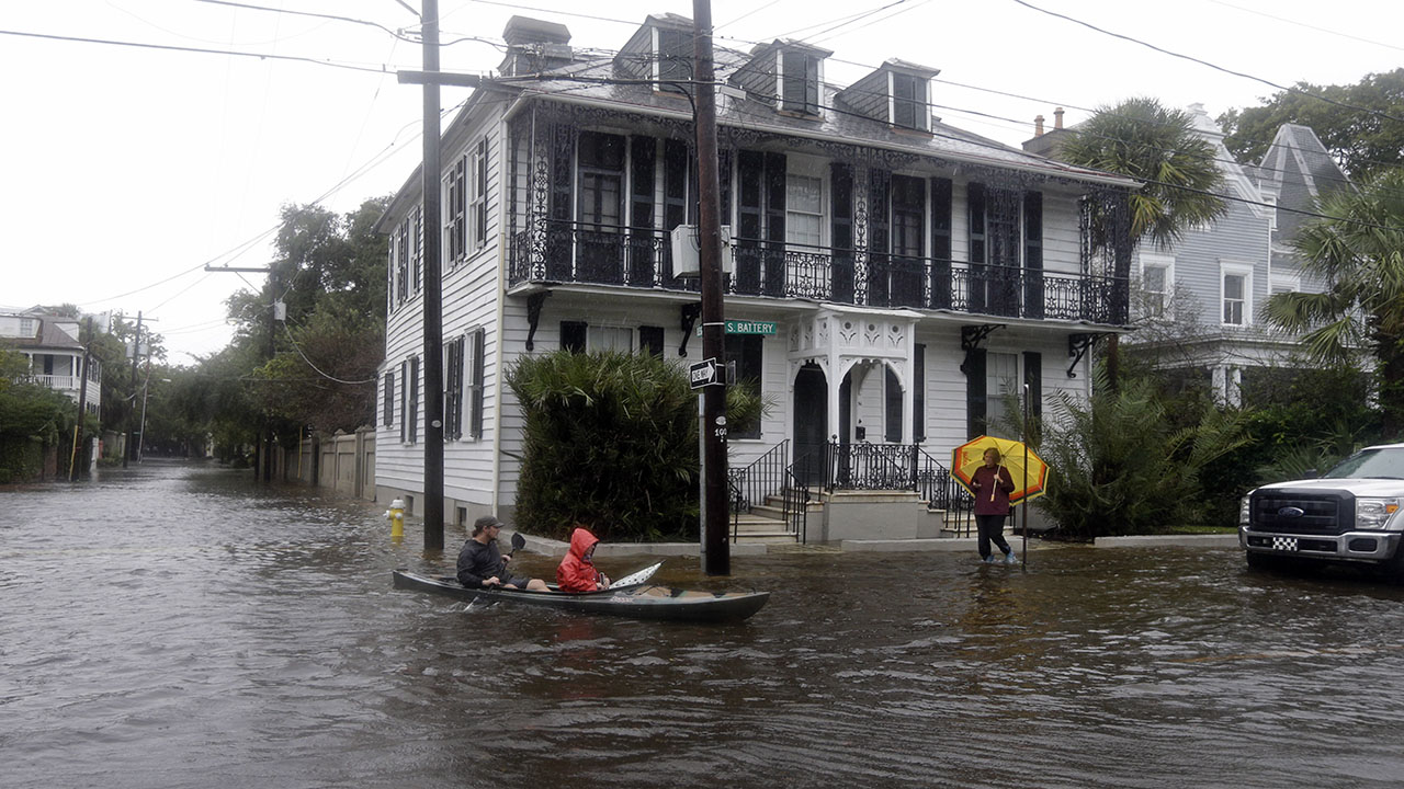 Paul Banker, left, paddles a kayak and his wife Wink Banker, as they takes photos on a flooded street in Charleston, S.C., Saturday, Oct. 3, 2015.