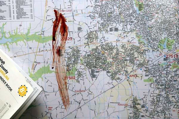 """<div class=""""meta image-caption""""><div class=""""origin-logo origin-image none""""><span>none</span></div><span class=""""caption-text"""">A streak of blood is seen on a large city map in the newsroom of The News & Observer offices (Photo/News & Observer)</span></div>"""