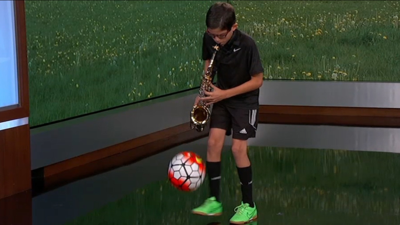 Kid kicks soccer ball while playing saxophone on 'Jimmy Kimmel Live!' Tuesday, October 6, 2015.
