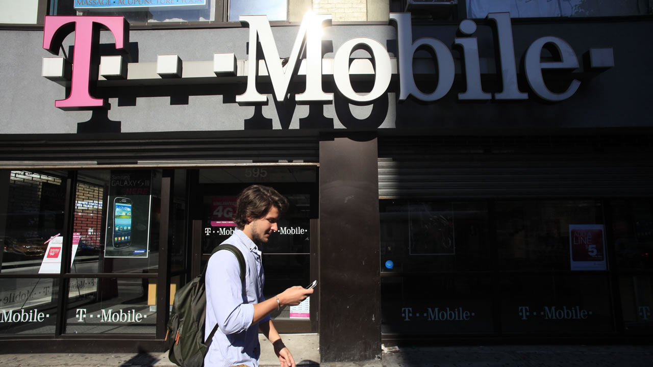 FILE-In this Wednesday, Sept. 12, 2012, file photo man using a cellphone passes a T-Mobile store, Wednesday, Sept. 12, 2012 in New York. (AP Photo/Mark Lennihan, File)