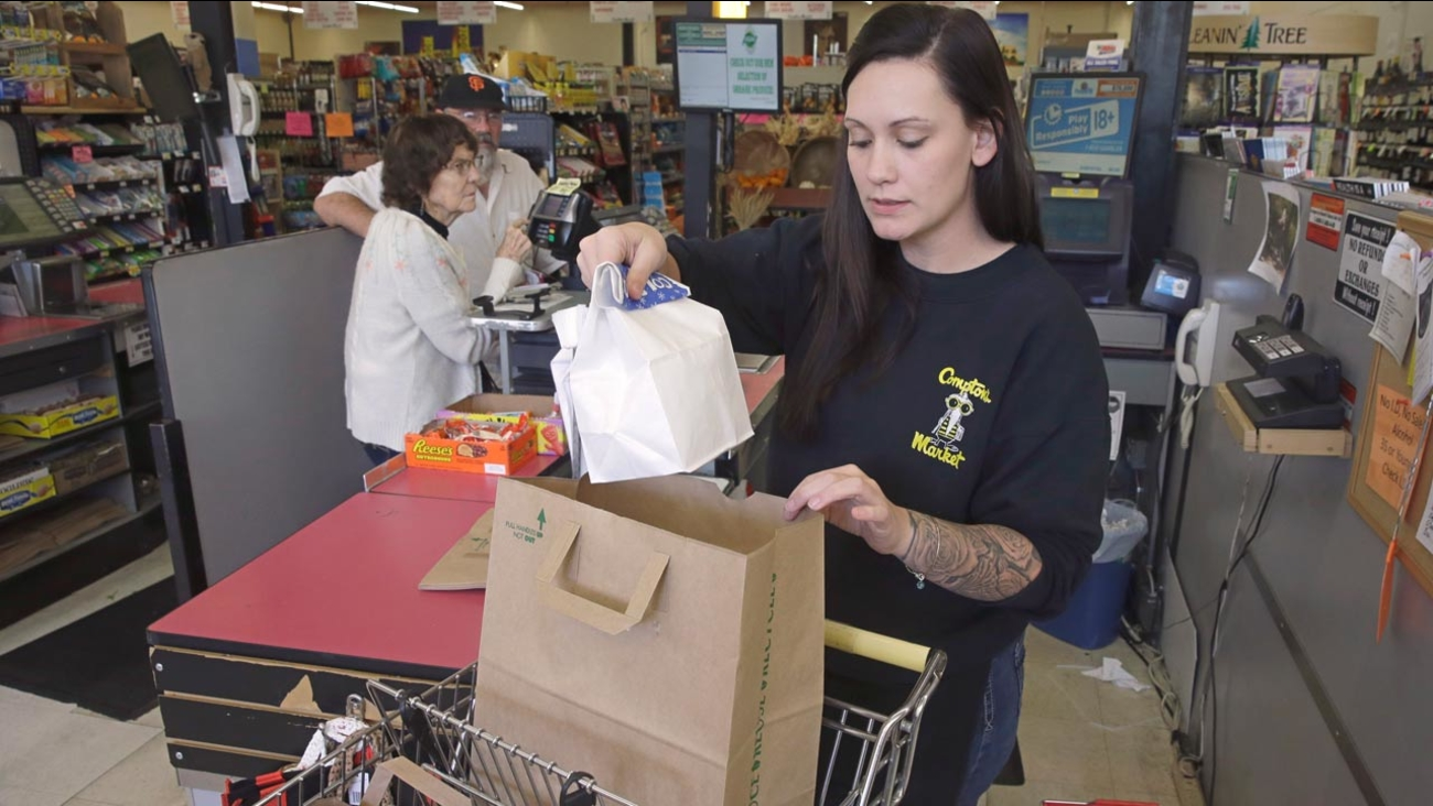 Checker Brittney Bounds bags groceries for customer Esther Franklin, left, at Compton's Market Tuesday, Oct 6, 2015 in Sacramento, Calif.