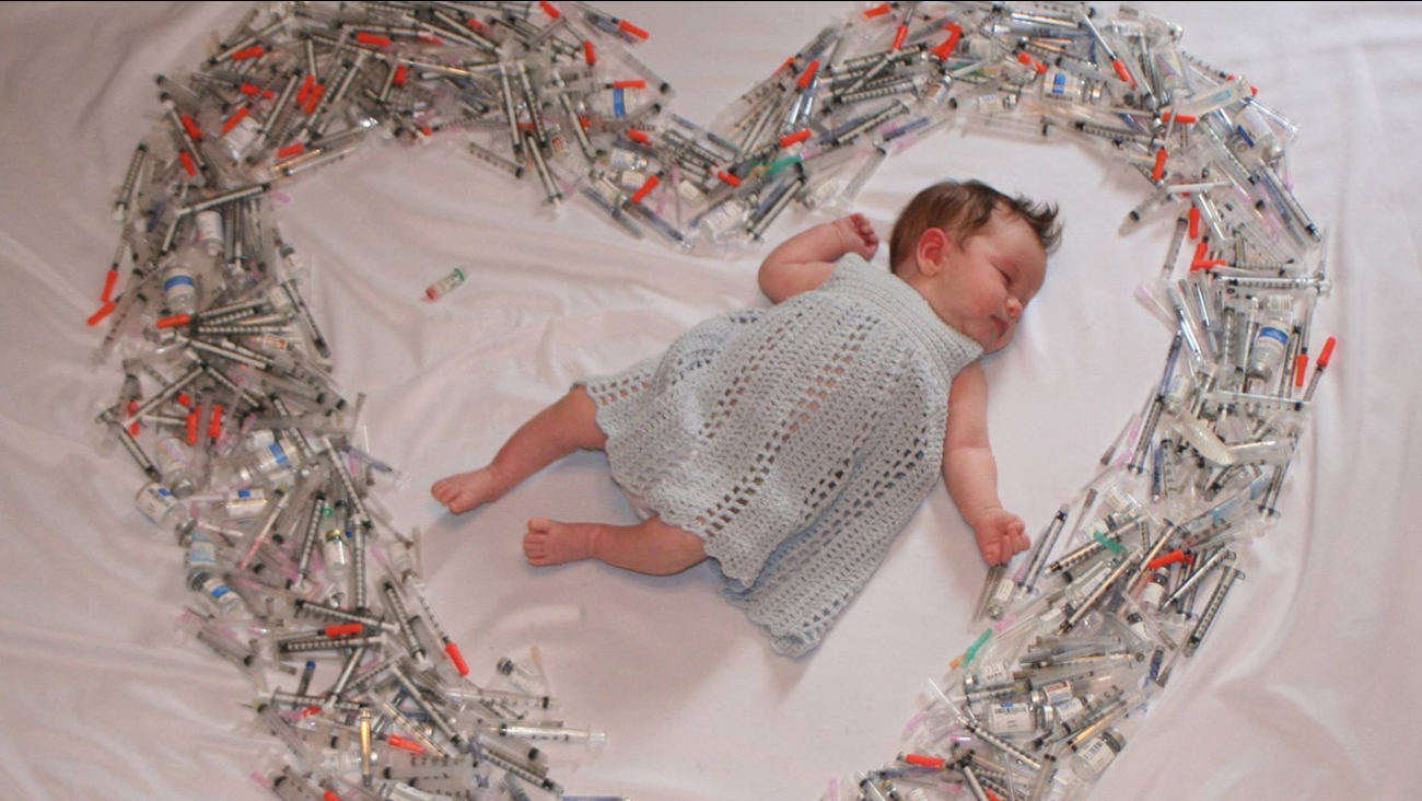A newborn baby surrounded by vials and syringes from its mother's IVF treatments.