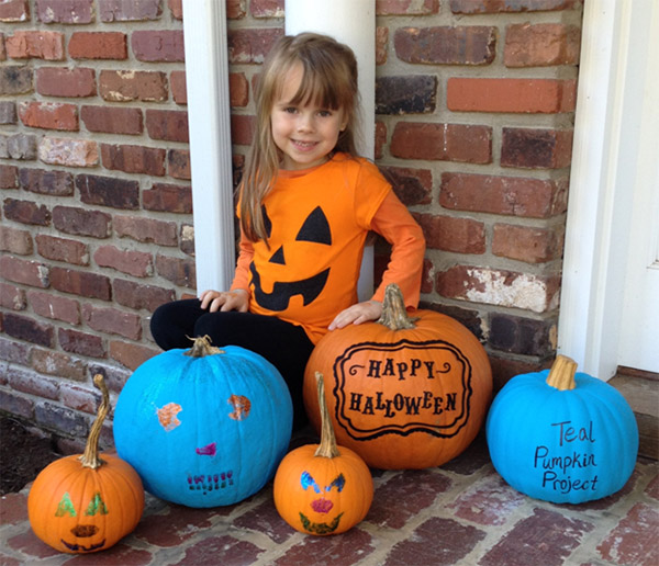 A little girl poses with a group of pumpkins, including two for the Teal Pumpkin Project.