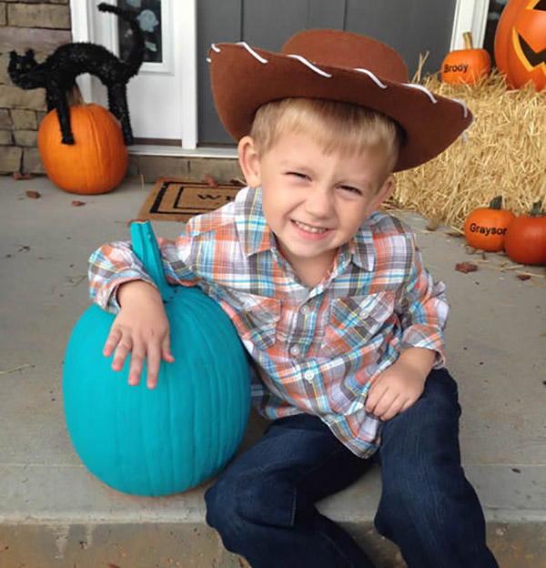 A little boy in a cowboy costume poses with a teal pumpkin.