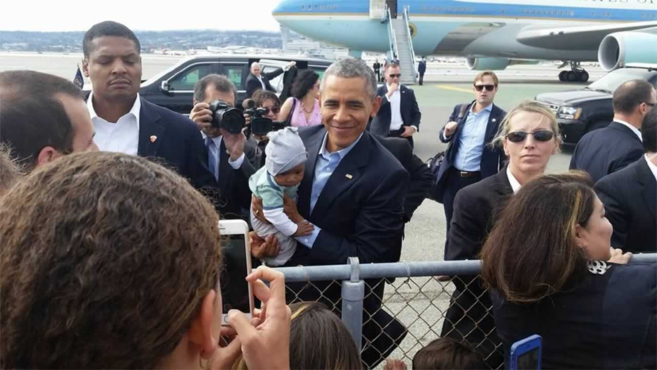 President Obama stopped to embrace a baby before boarding his flight at SFO on Saturday, October 11, 2015.