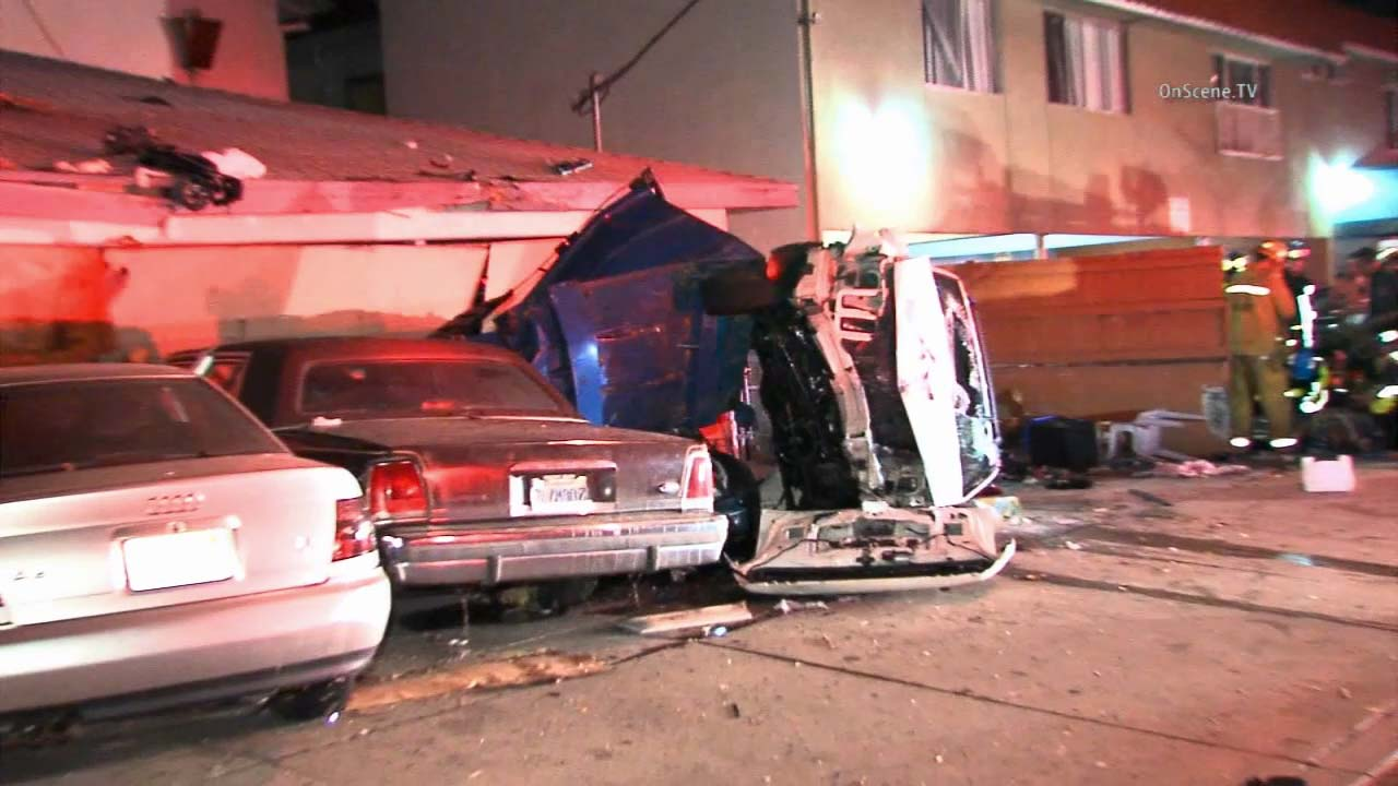 Two cars are seen crashed onto a row of parked cars in the city of Lawndale early Sunday, Oct. 11, 2015.