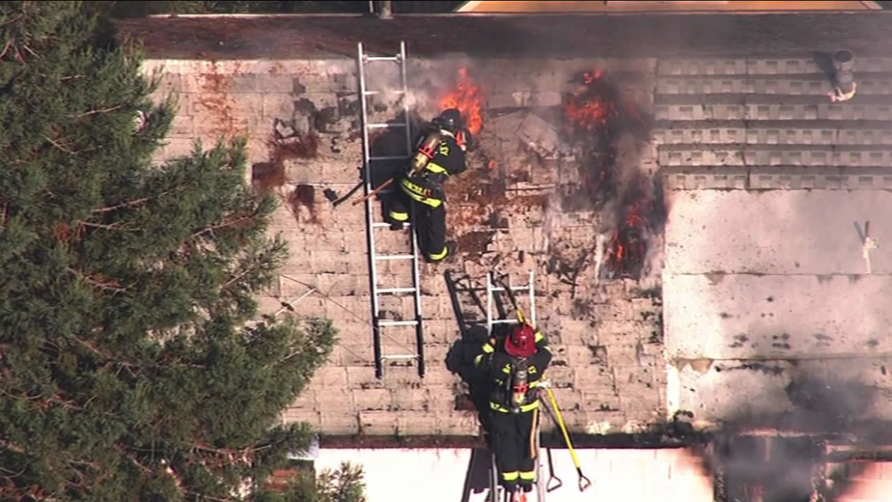 Berkeley firefighters work to put out a two-alarm house fire on Tuesday, October 13, 2015.
