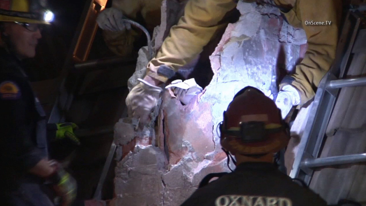 Firefighters work to rescue a teen, 15, from a chimney in a leasing office in Oxnard in the early morning hours of Wednesday, Oct. 14, 2015.