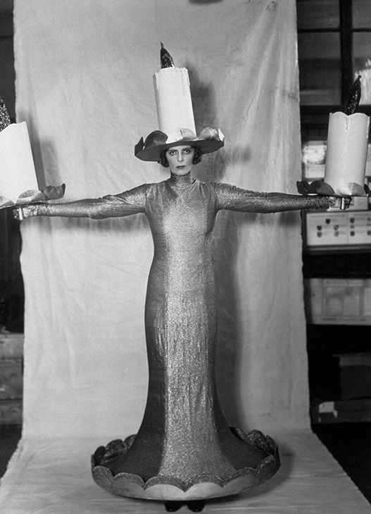"""<div class=""""meta image-caption""""><div class=""""origin-logo origin-image none""""><span>none</span></div><span class=""""caption-text"""">October 10, 1930: The Hon Mrs Roland Cubitt dressed as 'Three Candles' in a costume made by L & H Nathan Ltd, for the """"Pageant Of The Superstitions"""" in London. (Sasha/Getty)</span></div>"""