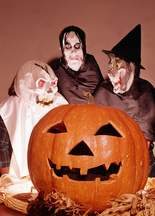 "<div class=""meta image-caption""><div class=""origin-logo origin-image none""><span>none</span></div><span class=""caption-text"">Portrait of three people in Halloween costumes as they pose behind a carved pumpkin, 1965. (Camerique/Getty)</span></div>"