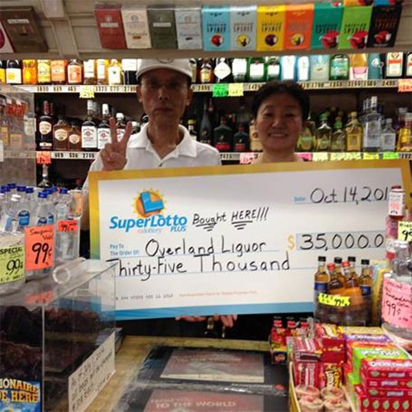 The owners of Overland Liquor hold up their $35,000 check for selling the winning ticket for the SuperLotto Plus for the Oct. 14, 2015 drawing.