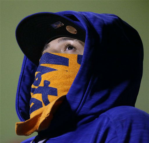 "<div class=""meta image-caption""><div class=""origin-logo origin-image none""><span>none</span></div><span class=""caption-text"">A fan tries to keep warm during the second inning of Game 2. (AP Photo/ David Goldman)</span></div>"