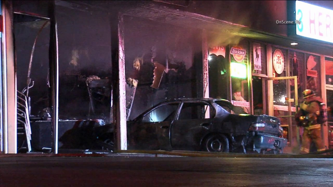 A car slammed into a yogurt shop and caught fire in the city of Commerce on Tuesday, Oct. 20, 2015.
