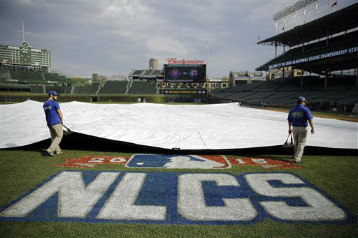 "<div class=""meta image-caption""><div class=""origin-logo origin-image none""><span>none</span></div><span class=""caption-text"">Workers pull the tarp off the infield at Wrigley Field before Game 3 of the National League championship series between the Mets and the Cubs. (AP Photo/David Goldman) (AP Photo/ David Goldman)</span></div>"