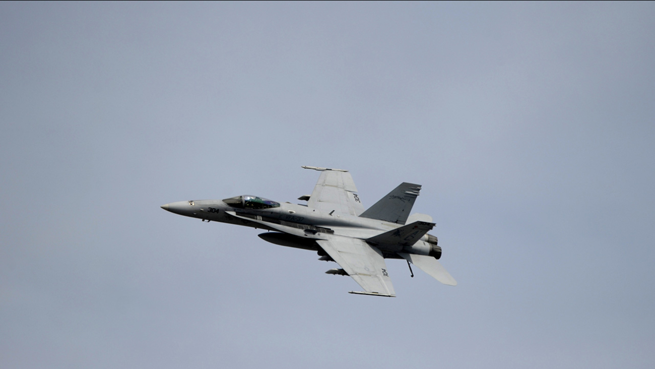 An F-18 military jet flies over the Daytona International Speedway.