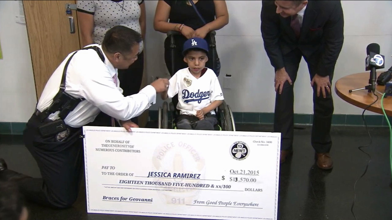 Geovanni Ramirez smiles for photos and shakes an LAPD officer's hand as he receives a more than $13,000 check and new leg braces on Thursday, Oct. 22, 2015.
