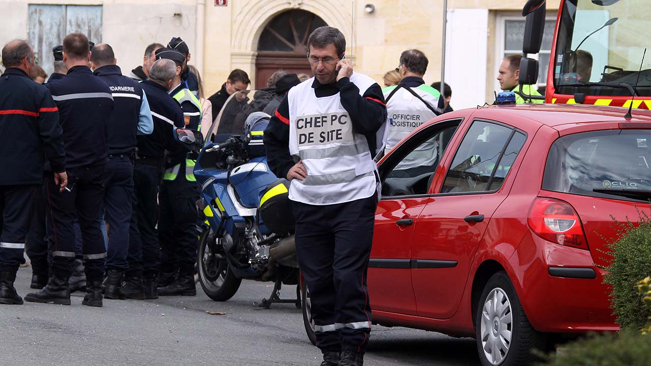 Police and firefighters are gathered in Puisseguin, near Bordeaux, southwestern France, following a road accident in which at least 42 people were killed, Friday, Oct. 23, 2015.