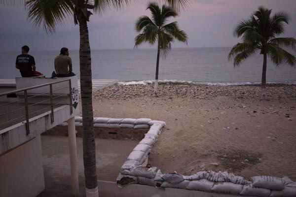 "<div class=""meta image-caption""><div class=""origin-logo origin-image none""><span>none</span></div><span class=""caption-text"">Two men sit out by the beach as hurricane Patricia nears in the Pacific resort city of Puerto Vallarta, Mexico, Thursday, Oct. 22, 2015. (AP Photo/ Cesar Rodriguez)</span></div>"