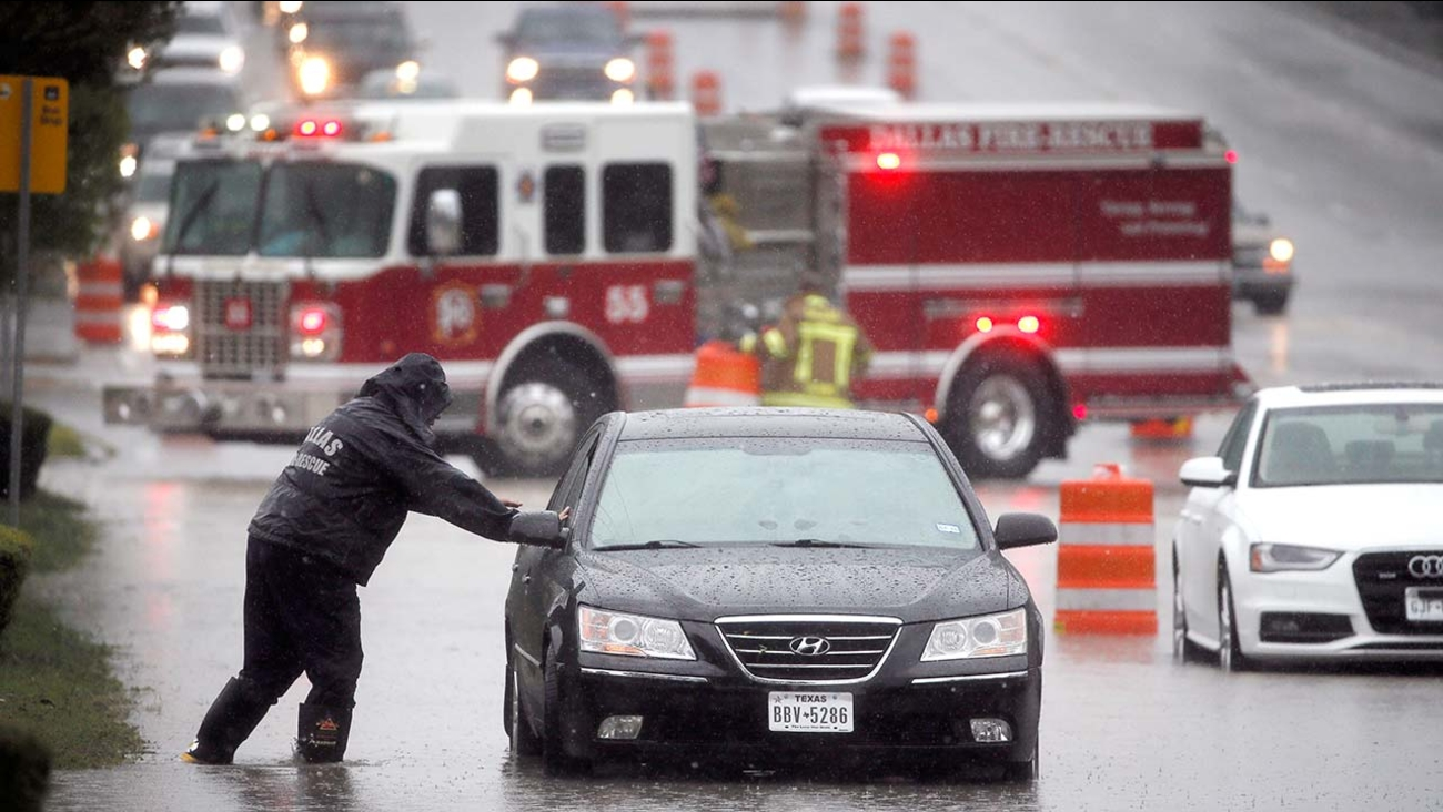 A Dallas Fire Rescue responder checks a stalled vehicle Friday, Oct. 23, 2015, in Dallas. Millions braced for storms that could spin off from massive Hurricane Patricia.