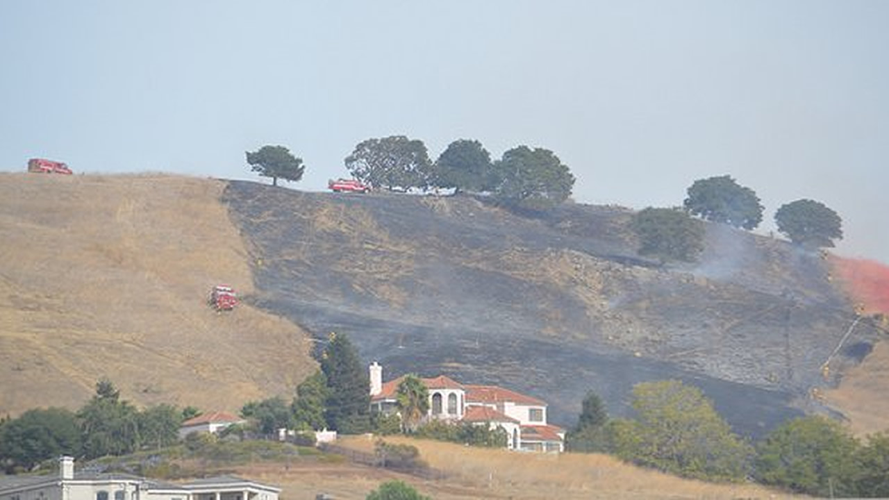 A small brush fire threatened homes in Milpitas, Calif., on Saturday, October 24, 2015.