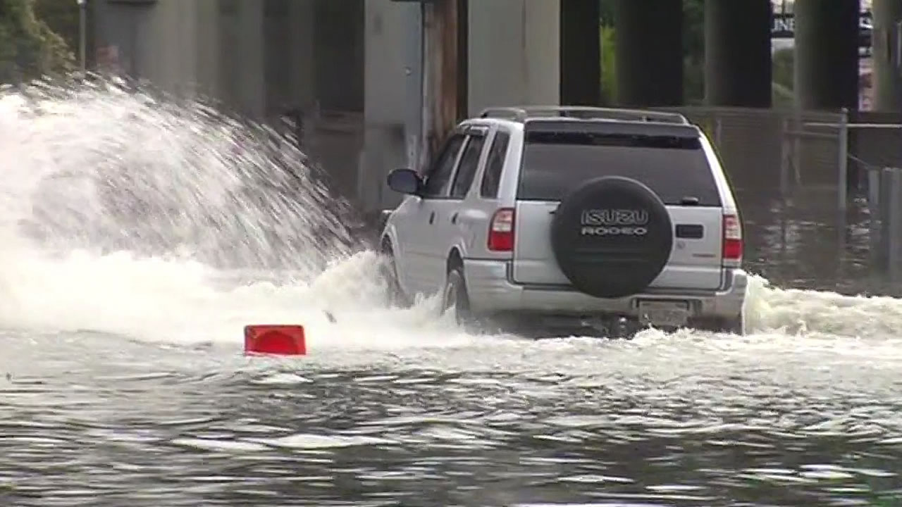 car drives through flood waters