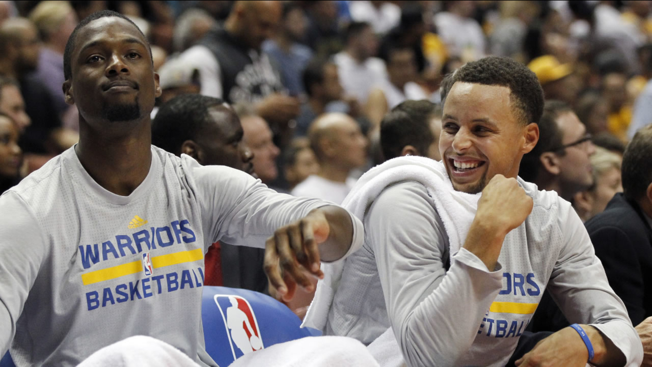 Golden State Warriors forward Harrison Barnes, left, makes guard Stephen Curry laugh on the bench during the second half of an NBA preseason basketball game Oct. 22, 2015.