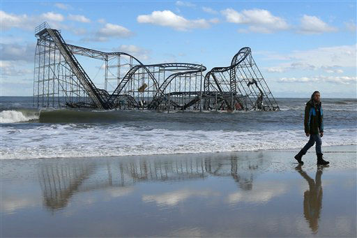 "<div class=""meta image-caption""><div class=""origin-logo origin-image none""><span>none</span></div><span class=""caption-text"">John Okeefe walks on the beach as a rollercoaster that once sat on the Funtown Pier in Seaside Heights, N.J., rests in the ocean on Wednesday, Oct. 31, 2012. (AP Photo/ Julio Cortez)</span></div>"