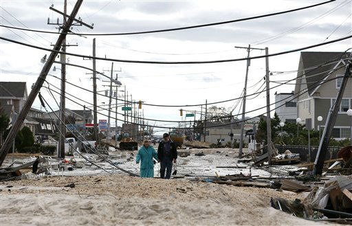 "<div class=""meta image-caption""><div class=""origin-logo origin-image none""><span>none</span></div><span class=""caption-text"">Robert Bryce, right, walks with his wife, Marcia Bryce, past downed utility poles and other debris from Superstorm Sandy on Route 35 in Seaside Heights, N.J. (AP Photo/ Julio Cortez)</span></div>"