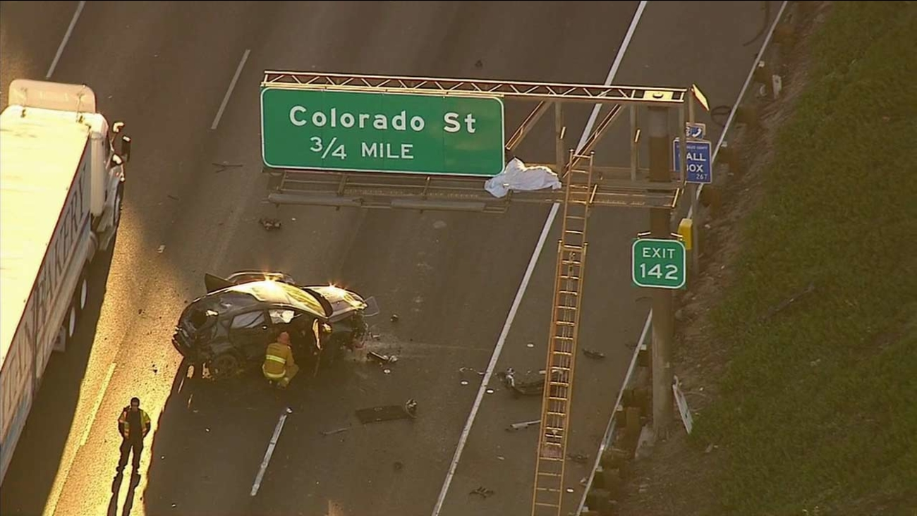 Authorities investigate the scene of a single-vehicle crash that ejected a driver onto a 5 Freeway sign in Glendale Friday, Oct. 30, 2015.