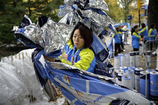 "<div class=""meta image-caption""><div class=""origin-logo origin-image none""><span>none</span></div><span class=""caption-text"">Volunteer Eri Miyasaka helps to arrange recovery blankets at the finish line before the start of the 2015 New York City Marathon. (AP Photo/ Seth Wenig)</span></div>"