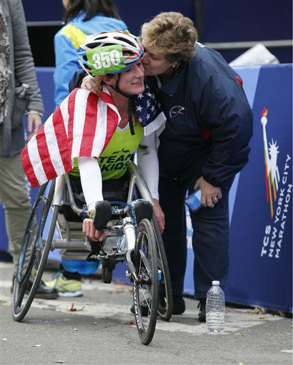 """<div class=""""meta image-caption""""><div class=""""origin-logo origin-image none""""><span>none</span></div><span class=""""caption-text"""">Donna McFadden, right, adoptive mother of Tatyana McFadden plants a kiss on her after the young woman set a course record winning the women's wheelchair division. (AP Photo/ Kathy Willens)</span></div>"""