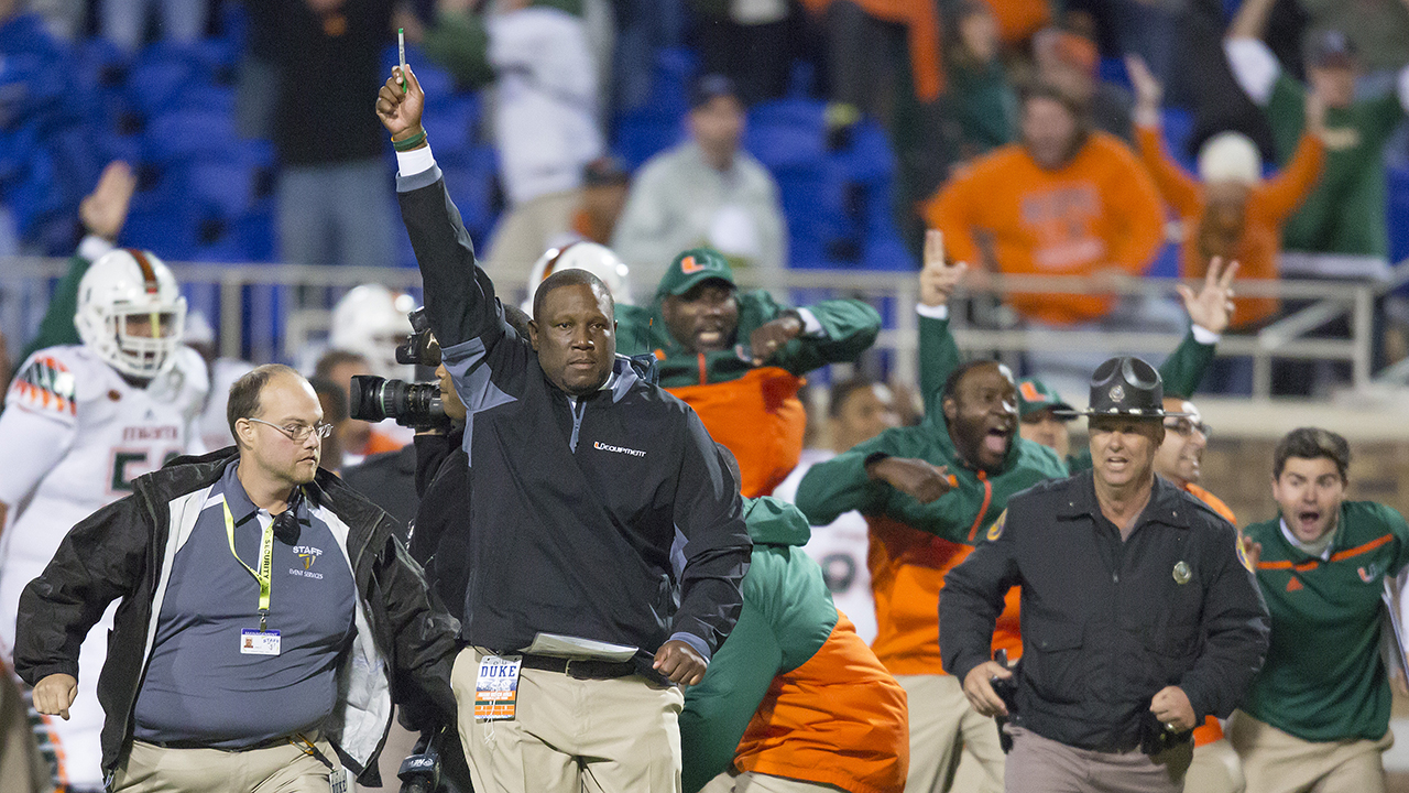 Miami's interim head coach Larry Scott raises his hand after defensive back Corn Elder returned a kickoff