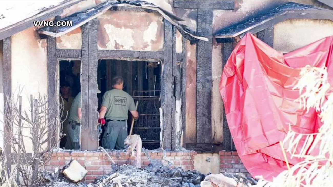 Authorities investigate a house fire near Hesperia that left 2 elderly people dead early Sunday, Nov. 1, 2015.