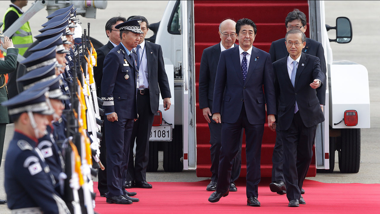 Japanese Prime Minister Shinzo Abe, second from right, is escorted by South Korean first vice foreign minister Lim Sung-nam upon his arrival at Seoul Airport.
