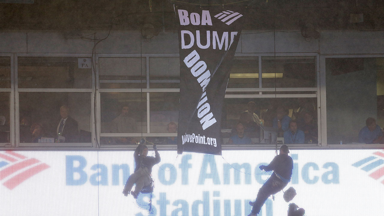 People hang from a banner at Bank of America stadium in the second half of football game between the Carolina Panthers and the Indianapolis Colts in Charlotte, NC.