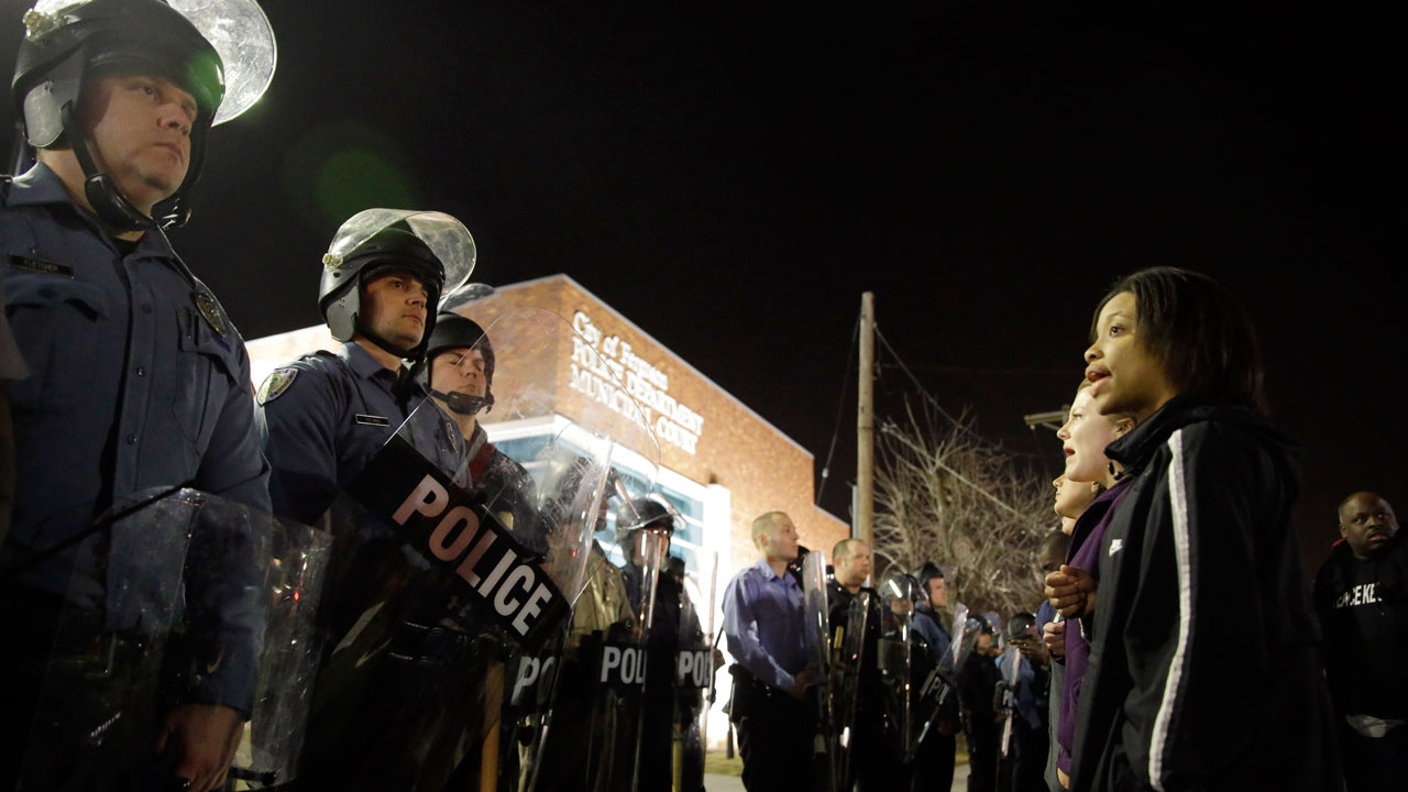 In this March 11, 2015 file photo, police and protesters square off outside the Ferguson Police Department in Ferguson, Mo.