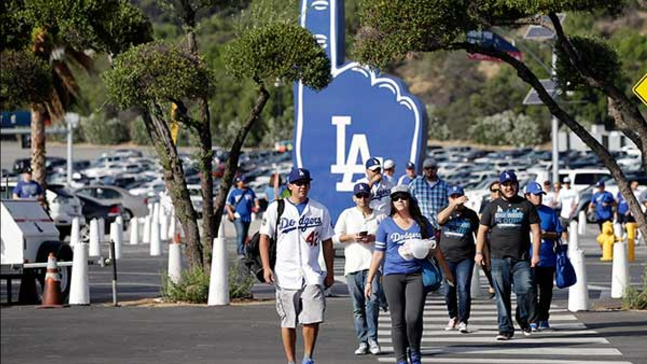 Fans walk in the parking lot of Dodger Stadium in Los Angeles on Thursday, Oct. 15, 2015.