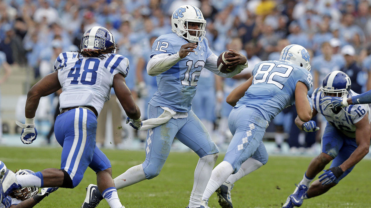 North Carolina quarterback Marquise Williams (12) finds some running room as Duke's Deion Williams (48) looks for the tackle during the first half