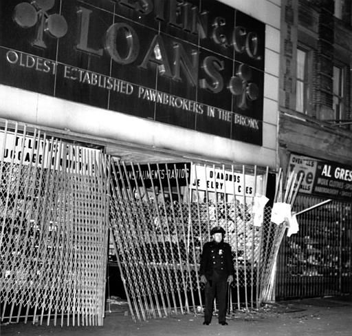 <div class='meta'><div class='origin-logo' data-origin='none'></div><span class='caption-text' data-credit='AP Photo/ File'>A policeman stands in front of a pawn shop in the Bronx area of New York that was looted Nov. 9, 1965 during a massive power blackout.</span></div>