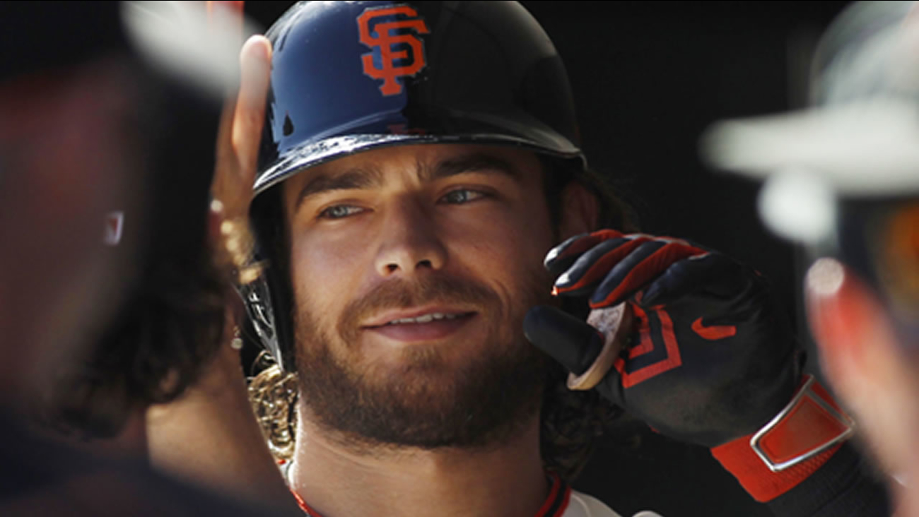 San Francisco Giants' Brandon Crawford smiles in the dugout after hitting a home run against the Rockies during the fourth inning of a baseball game, Saturday, Oct. 3, 2015.
