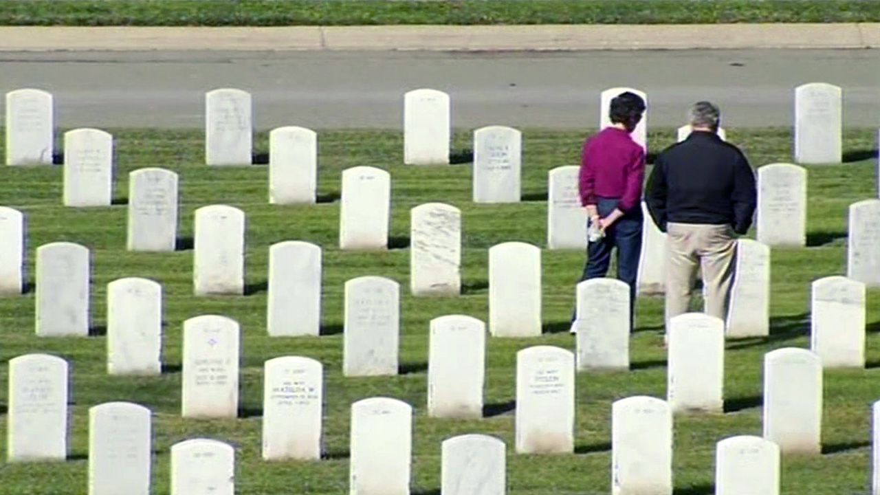 FILE -- Man and woman honor veteran at cemetery in Bay Area.